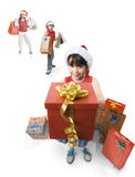 Giving a present. Little girl giving a present to someone, while other childs waits behind her Royalty Free Stock Images