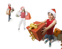 Giving a present. Little girl giving a present to someone, while other childs waits behind her Royalty Free Stock Photos