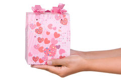 Giving present. Both hand holding the present in horizontal position, shot against very bright white background Royalty Free Stock Photos