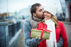Giving present. Image of affectionate guy kissing his girlfriend while giving her present outside Royalty Free Stock Image