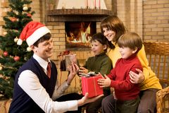 Giving presents. Photo of happy father giving Christmas gifts to surprised sons on holiday eve Stock Images
