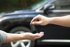 Giving and receiving car key. Hands giving and receiving car key Stock Photography