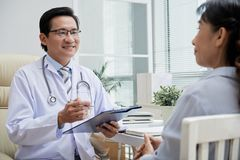 Giving Recommendations to Patient. Friendly middle-aged physician wearing white coat sitting opposite senior patient and giving recommendations while having royalty free stock photos