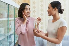 Giving Recommendations to Pretty Young Client. Profile view of friendly cosmetologist recommending moisturizing cream to attractive Asian client while having royalty free stock photo
