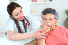 Giving senior woman drink water. Giving senior women a drink of water royalty free stock photography