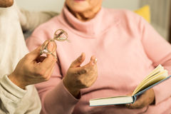 Giving senior woman reading glasses stock image