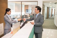 Giving smart card. Beautiful receptionist giving smart card to the businessman Royalty Free Stock Image