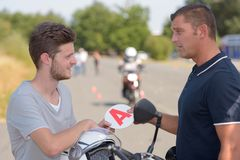 Giving sticker to motorbike student Royalty Free Stock Photos