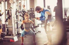 Giving support. Trainer giving support sportswoman at gym stock photos