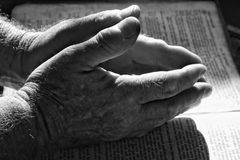 Giving Thanks. Praying hands folded on a bible with dramatic lighting Stock Images