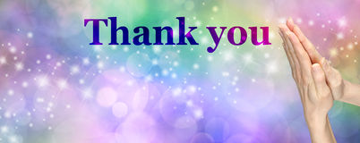 Giving Thanks Banner. Female hands in prayer position on a multicolored bokeh and sparkles background with the word 'Thank you' and plenty of copy space stock images