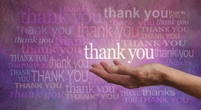 Giving Thanks. Female hand outstretched with palm up and the word 'Thank you' hovering above with a stone effect purple and pink background covered in different Stock Photography
