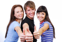 Giving the thumbs-up sign. Three young teenagers laughing and giving the thumbs-up sign Royalty Free Stock Image