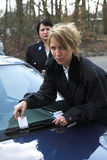 Giving a ticket. Female police officer putting a parking ticket under the windscreenwiper Royalty Free Stock Image