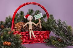 Giving time message held by wooden jointed manikin doll sitting in red basket full of pinecones and pine garland wearing Santa hat. Giving time message held by royalty free stock image