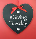 Giving Tuesday message greeting on black heart shape blackboard Royalty Free Stock Photos