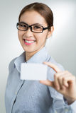 Giving a visiting card. Vertical portrait of a smiling businesswoman giving an id-card on the foreground Royalty Free Stock Photos