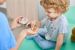 Giving Vitamins to Curly Little Patient stock photography