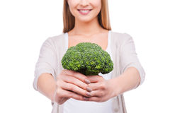 Giving you a pit of vitamins. Cropped image of beautiful young woman stretching out broccoli and smiling while standing against white background Royalty Free Stock Photos