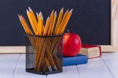 Giz de quadro-negro do fundo, livros, lápis e maçã foto de stock royalty free