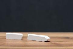 Giz quebrado na mesa do professor na frente do quadro-negro fotografia de stock