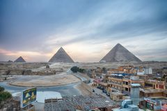 View on the town and the Great Pyramids in the evening. Giza, Cairo. Egypt - March 24, 2019: View on the town and the Great Pyramids in the evening, africa royalty free stock photo