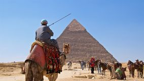 Giza, Egypt - March 2018: Camel rides around the Pyramid of Khafre in Giza, Egypt. Giza, Egypt - March 2018: Camel rides around the Pyramid of Khafre in Giza Royalty Free Stock Images