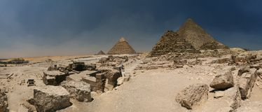 Giza plateau - with all three big pyramids (the darker one close to the centre is small pyramid for a queen) and a Sphinx on the l Royalty Free Stock Images