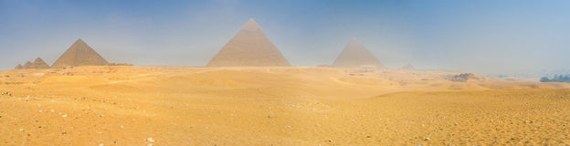 The Giza Plateau. Panorama of all Giza Pyramids in the light hazeof the desert sand, Egypt Royalty Free Stock Image