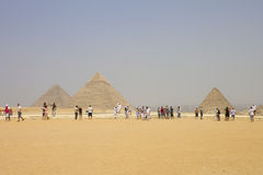 Giza - pyramids with the tourists admiring them Royalty Free Stock Photos
