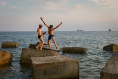 Two friends are playing on the beach, jumping on concrete blocks stock photos