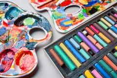 Gizes pasteis coloridos e uma paleta das pinturas em uma luz - fundo cinzento criação Imagem de Stock Royalty Free