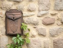 Gjorde den bruna rostiga brevlådan för antikviteten på en sten väggen royaltyfria foton