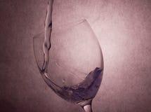 Gjuta vatten till vinrankaexponeringsglas Arkivbild
