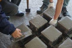 Gjuter konkret rollbesättning för kuben vid stål och arbetaren som avslutar bästa yttersida vid mursleven arkivfoton