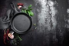 Gjutjärnpanna och kryddor på kulinarisk bakgrund för svart metall royaltyfri bild