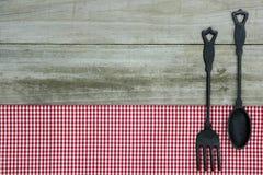 Gjutjärnsked och gaffel på röd ginghambordduk med wood bakgrund Royaltyfria Bilder
