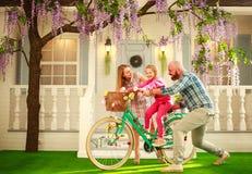 Glückliche Eltern mit einem Kind, Tochter, lernen, ein Fahrrad, Familienlebensstil-Sommerferien zu Hause zu reiten lizenzfreie stockfotografie