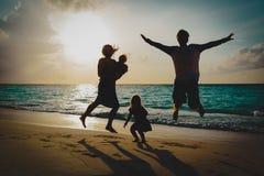 Glückliche Familie mit Kindern genießen an Ferien, Spiel auf Sonnenuntergangstrand lizenzfreie stockfotografie