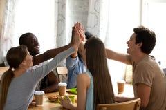 Glückliche gemischtrassige Freunde, die hoch fünf, grüßend am Treffen im Café geben lizenzfreies stockfoto