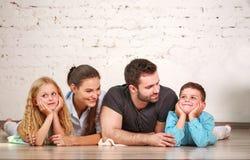 Glückliche träumerische junge Paare von Eltern mit ihren zwei Kindern zu Hause zusammen stockbild