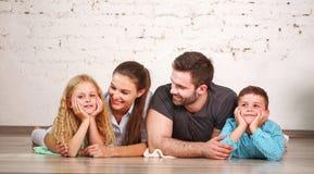 Glückliche träumerische junge Paare von Eltern mit ihren zwei Kindern zu Hause zusammen lizenzfreies stockbild