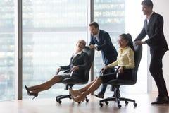 Glückliche verschiedene Angestellte, die den Spaß fährt auf Stühle im Büro haben lizenzfreie stockbilder