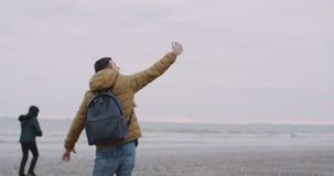 Glücklicher freudig erregt Tourist, der glücklich auf einem großen Strand mit einer Seeansicht, er ein Telefon und genommenen sel stock footage