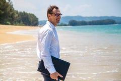 Glücklicher Geschäftsmann im Hemd mit einem Laptop und mit Gläsern gehend auf den Strand lizenzfreie stockfotografie