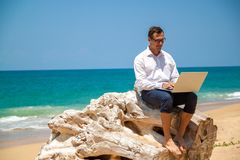 Glücklicher Geschäftsmann im Hemd mit einem Laptop und mit Gläsern gehend auf den Strand lizenzfreies stockbild