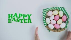 Glücklicher Ostern-Text, Frau, die Korb mit farbigen Eiern auf weißen Hintergrund setzt stock video footage