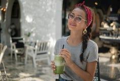 Glückliches hübsches junges Modell wirft mit Cocktail in den Händen draußen auf stockbilder