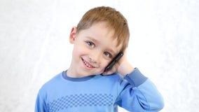 Glückliches Kind, das an einem Handy auf einem weißen Hintergrund, Freude, Lächeln und positive Gefühle zeigend spricht stock footage