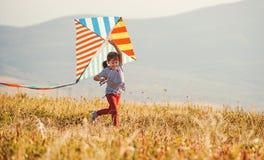 Glückliches Kindermädchen, das draußen mit Drachen bei Sonnenuntergang läuft stockbilder